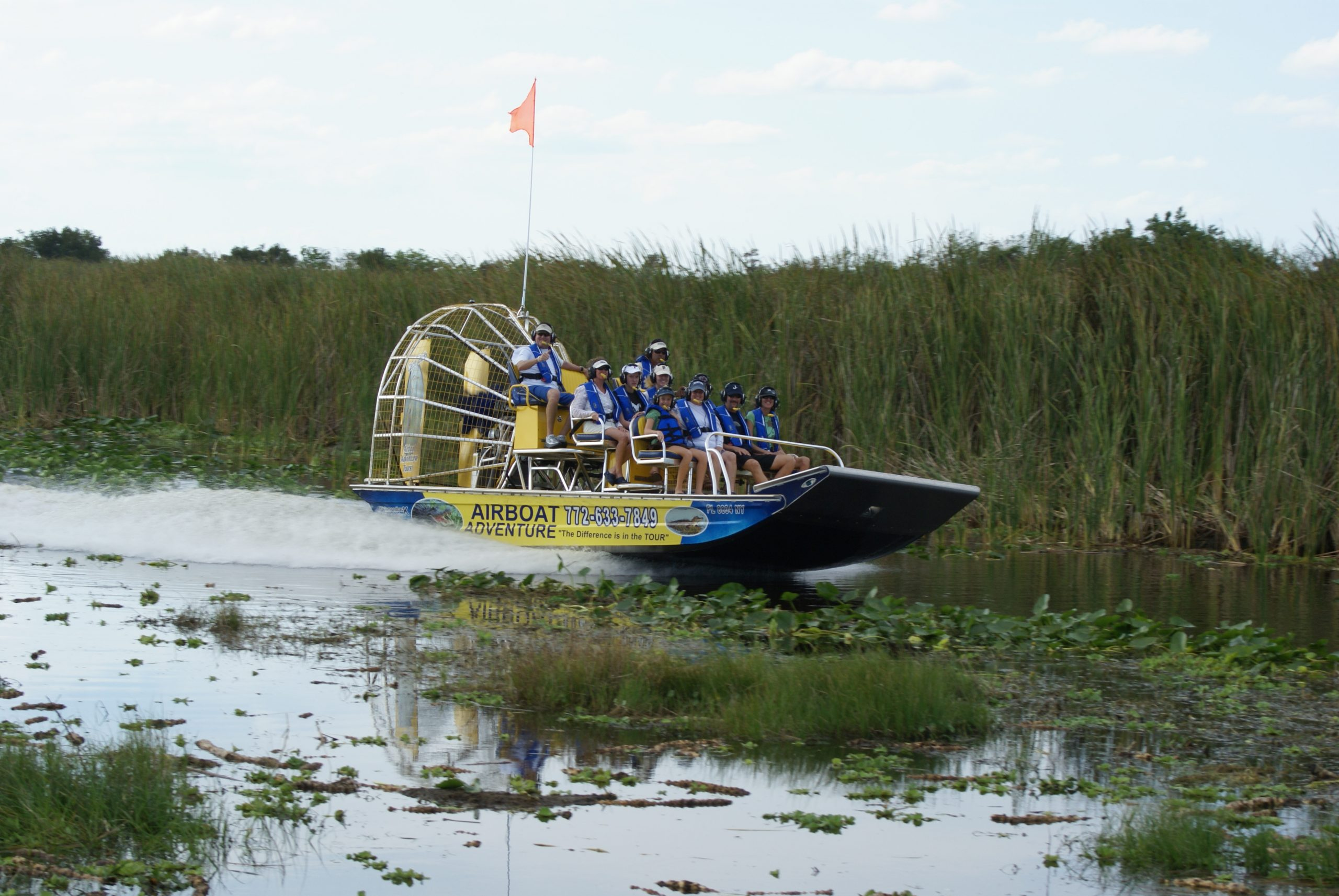 Airboat on marsh speeds by